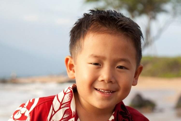 Smiling boy wearing a traditional red and white Hawaiian shirt on a beach.