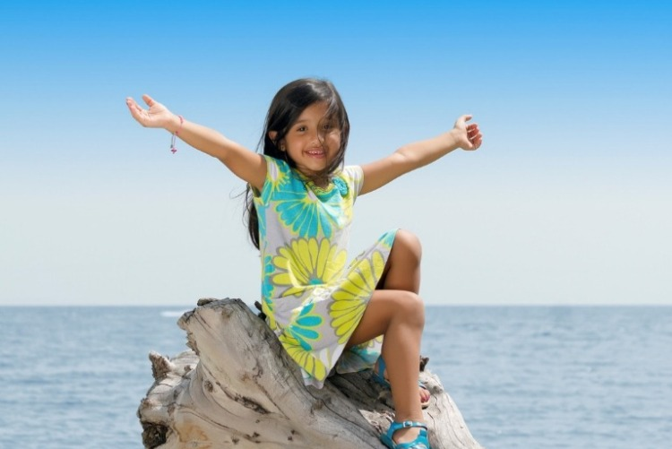 Young girl in floral Hawaiian dress, sitting on driftwood with arms outreached, and the ocean in the background.