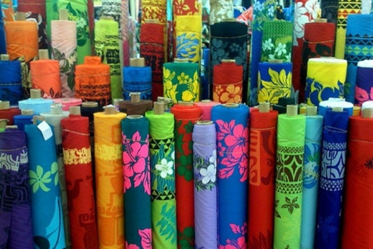 More than 60 rolls of colorfull Hawaiian print fabrics standing upright.