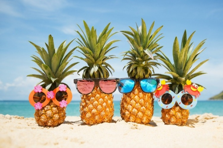 Four humorous looking pineapples decorated with tropical sunglass accessories, sitting alongside each other on a beach.