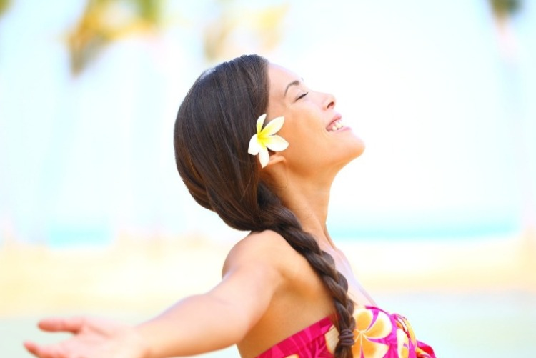 Pretty young woman with a white and yellow hibiscus flower in her hair, wearing a classic Hawaiian dress, looking to the sky with eyes closed, smiling, and arms outstretched.
